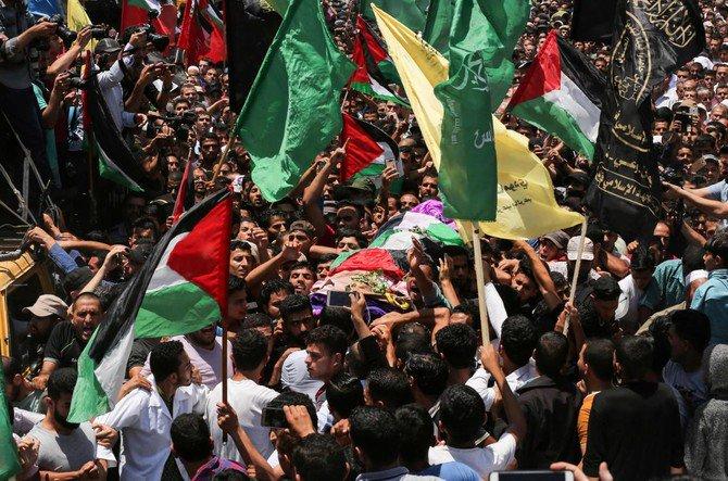 Para pelayat Palestina membawa tubuh Razan Al-Najjar berusia 21 tahun selama pemakamannya setelah dia ditembak mati oleh tentara Israel, di Khan Yunis dekat pagar perbatasan Gaza. (AFP)