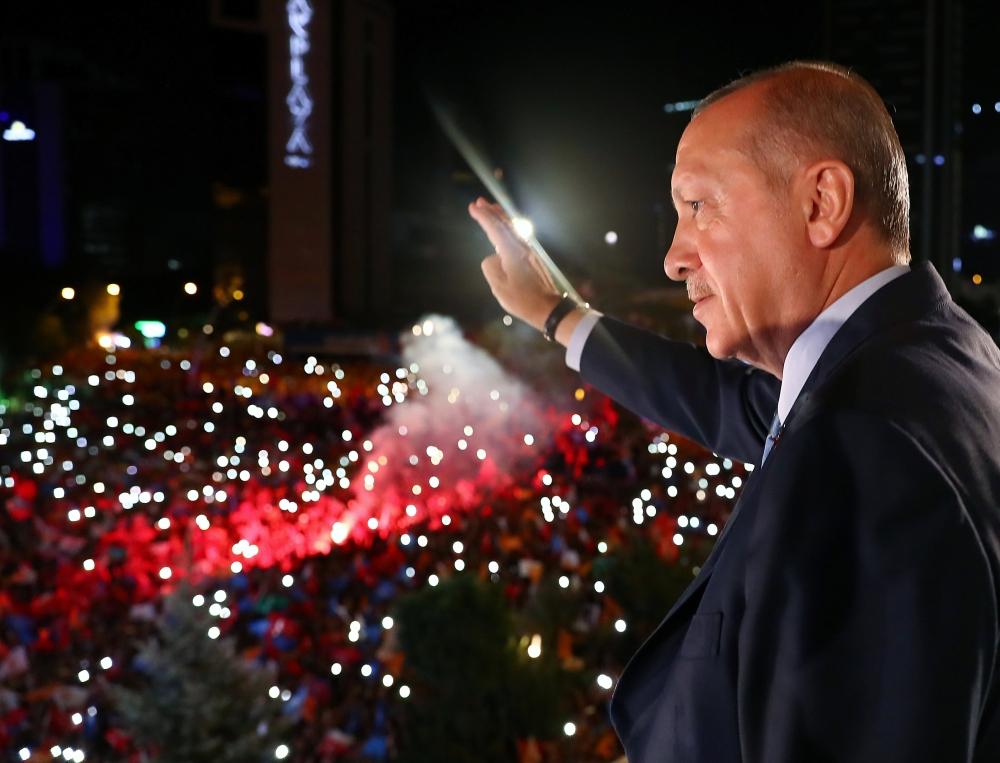 Presiden Turki Tayyip Erdogan menyapa para pendukungnya dari balkon markas Partai AK yang berkuasa di Ankara, Turki, Senin pagi. - Reuters