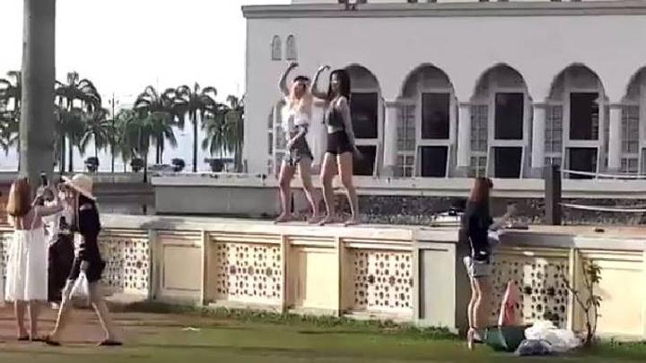 Dua wisatawan China menari di atas tembol Masjid Kinabalu